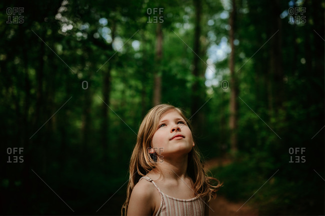 Portrait of a girl looking up in the woods