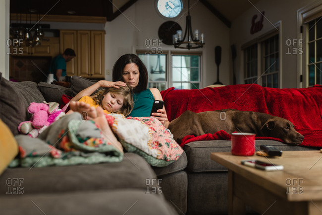 A mother, daughter and dog lying on a couch in the morning