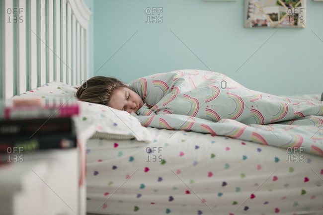 A young girl lying in her bed in the morning