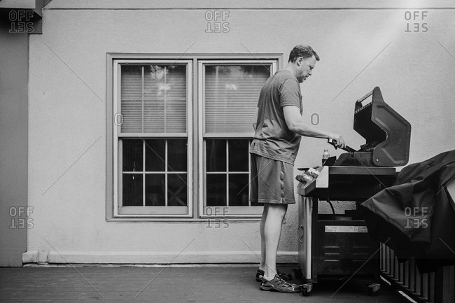 Man barbecuing outside of his home on a deck