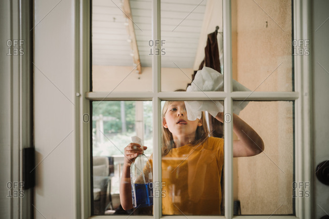 Little girl cleaning windows at her home