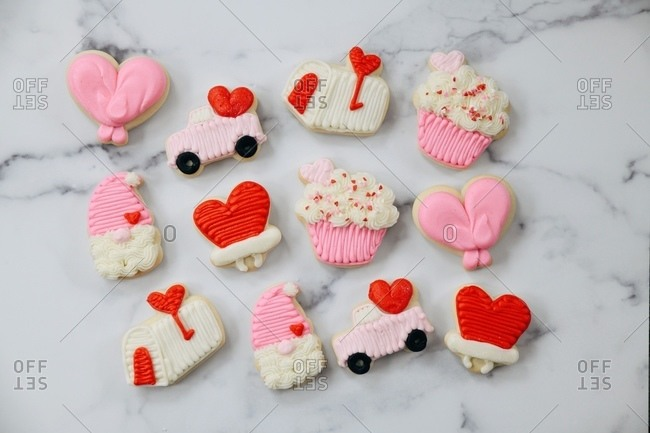 Variety of Valentine's Day sugar cookies on white marble surface