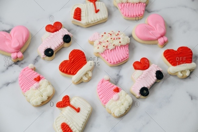 Close up of Valentine's Day sugar cookies on white marble surface