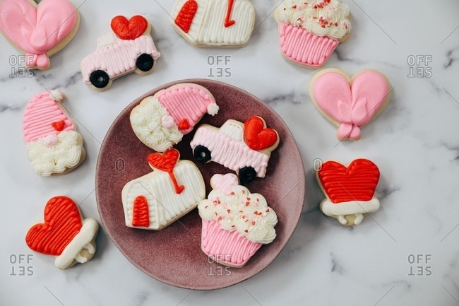 Variety of Valentine's Day sugar cookies on white marble surface and plate