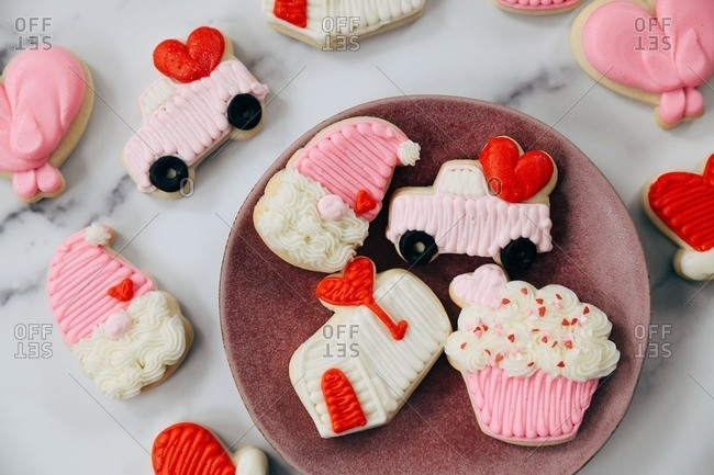 Valentine's Day sugar cookies on white marble surface and plate