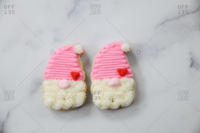 Close up of two gnome sugar cookies on white marble surface