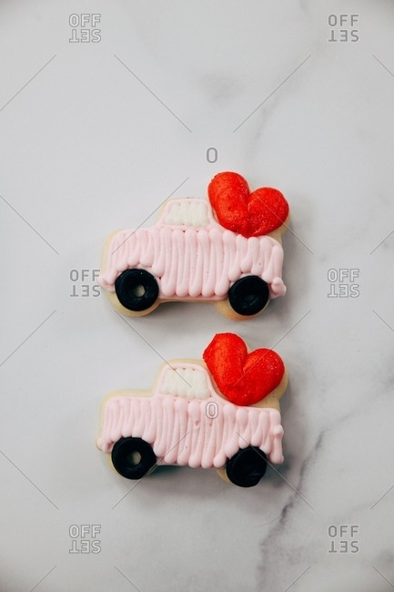 Close up of two truck with heart sugar cookies on white marble surface