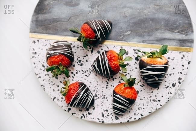 Gourmet chocolate covered strawberries on stone platter