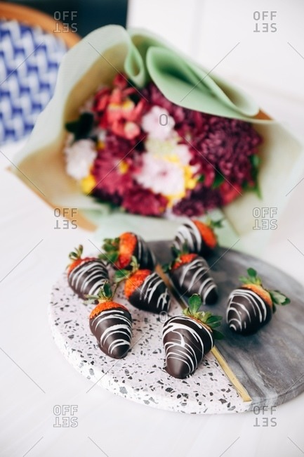 Gourmet chocolate covered strawberries on stone platter beside bouquet of flowers