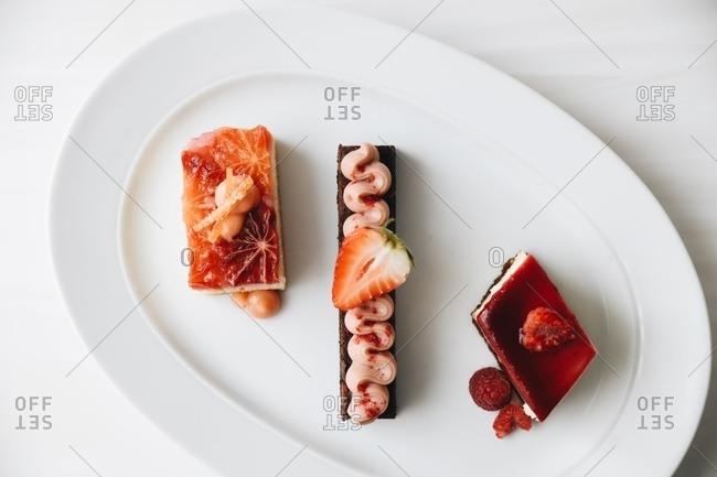 Three gourmet desserts served on platter