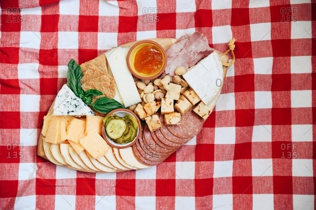 Charcuterie board served on red checkered tablecloth