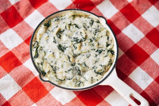 Spinach dip served on red checkered tablecloth