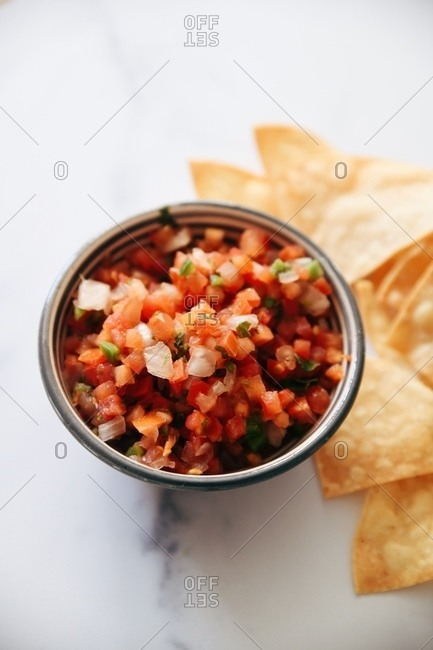 Overhead view of finely diced salsa served with chips on marble surface