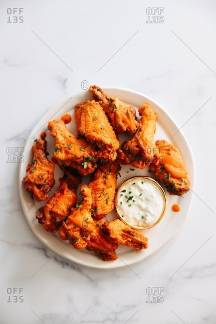 Spicy buffalo chicken wing appetizer on marble surface viewed from above