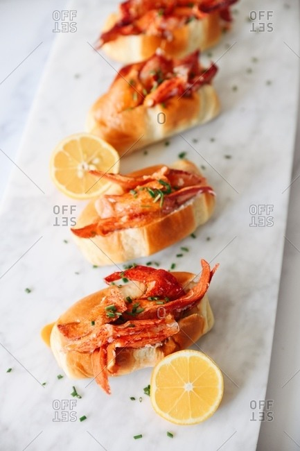 Top view of crab rolls on white marble with lemon and chives