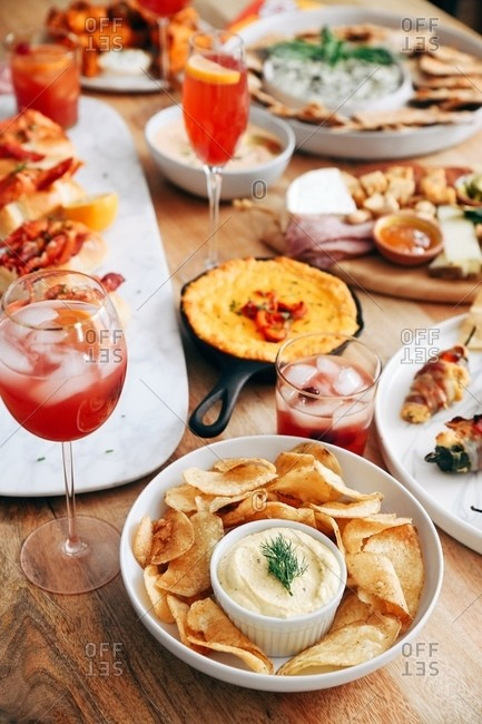 Variety of appetizer served on wooden table with cocktails and crab rolls