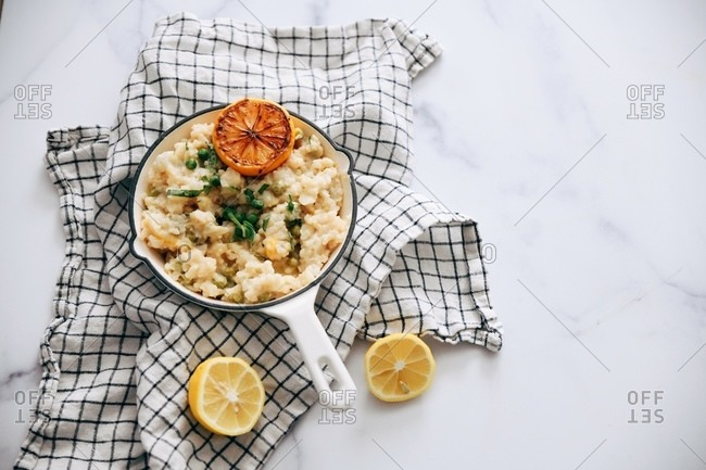 Overhead view of risotto and peas with roasted lemon in a white skillet on white marble surface with towel