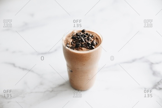 Chocolate protein smoothie topped with chocolate chips on white marble surface