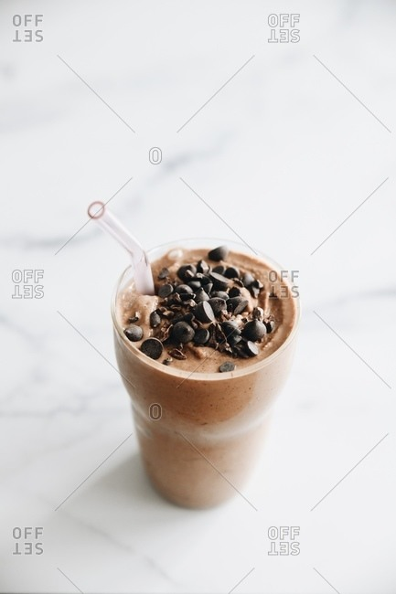 Chocolate protein smoothie topped with chocolate chips on white marble surface with straw