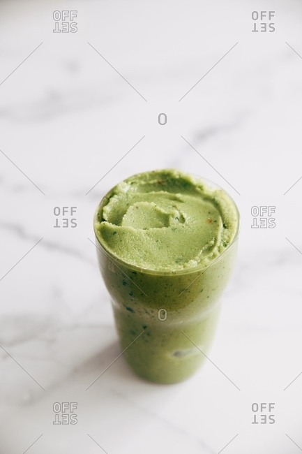 A green healthy smoothie on white marble surface