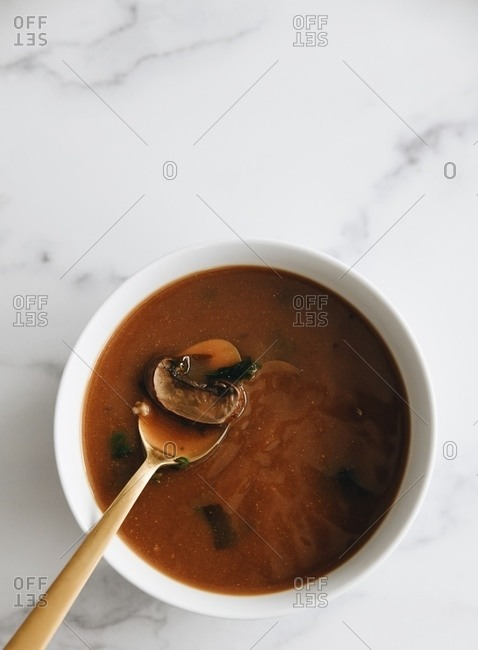 Bowl of mushroom soup served on white marble surface