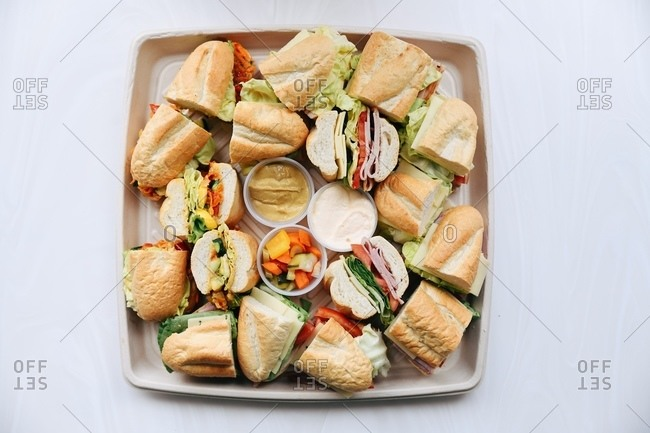 Platter filled with cut subs on white surface