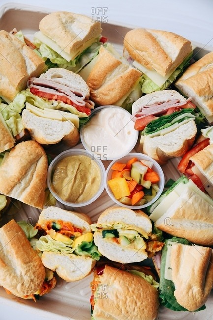Top view of a platter filled with cut subs on white surface