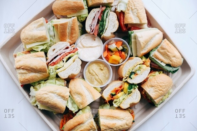 Overhead view of a platter filled with cut subs on white surface