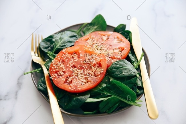 Salad with tomato on white marble surface with gold utensils
