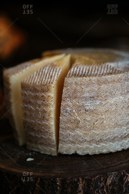 An aged cheese wheel being sliced