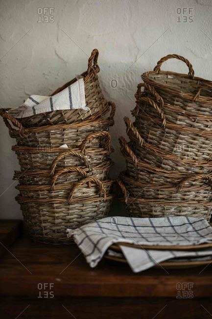 Stack of baskets and linen napkins on rustic wooden table