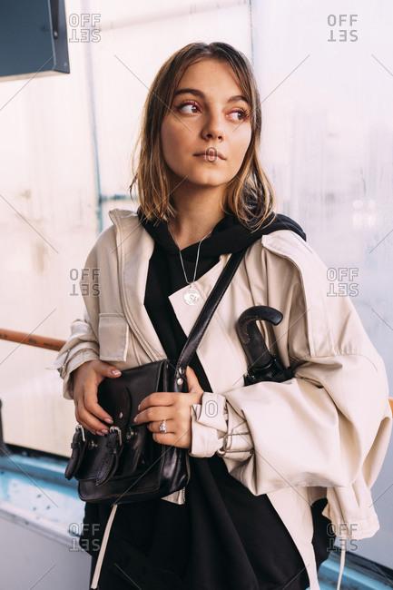 Woman on public transport wearing a white jacket