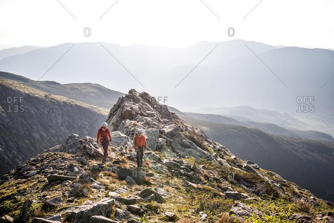 Man and woman walking on ridge during morning in mountains