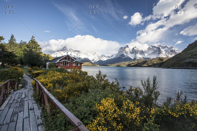 A small red building in front of the peaks of Torres del paine