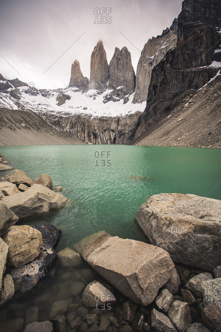 The towers of Torres del paine behind their green alpine lake