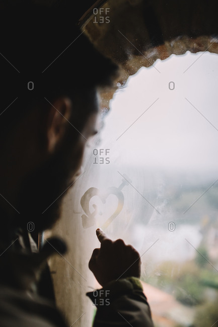 Man drawing with his finger a heart in wet window