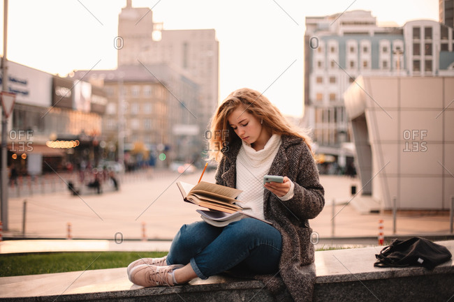 Serious teenage student girl learning while sitting in city in autumn