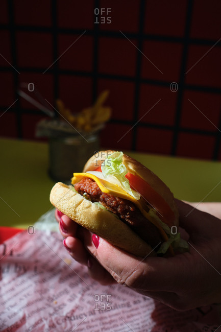 Hands with painted nails holding a cheeseburger, lettuce, tomato