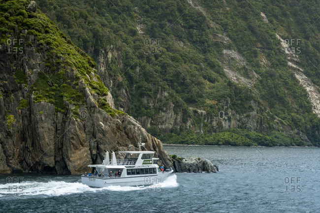 Milford sound, southland, new zealand - march 10, 2019: tourist boat at milford sound against mountain, new zealand