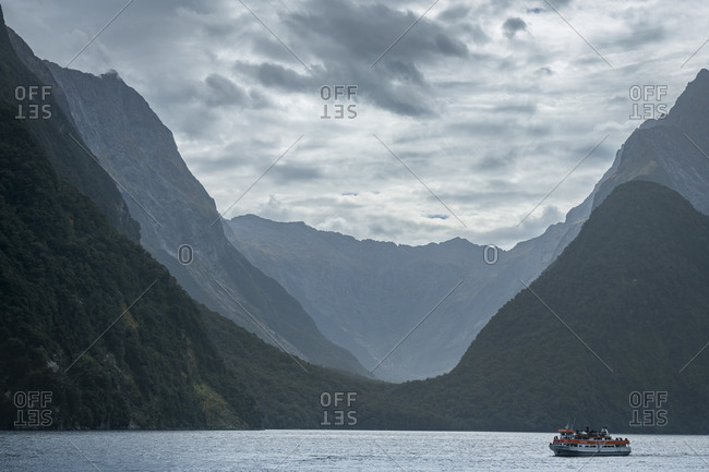 Milford sound, southland, new zealand - march 10, 2019: tourist boat at milford sound against sky, new zealand