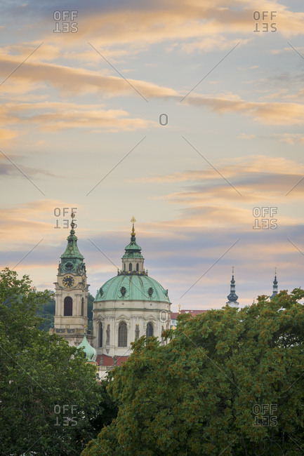 Towers of st. nicholas church in lesser quarter against sky during sunset, prague, Czech republic