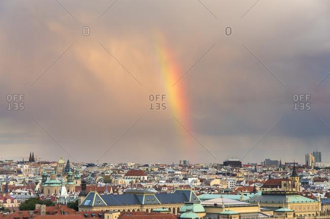 Rainbow over prague skyline against cloudy sky during sunset, Czech republic
