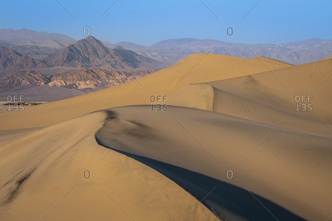 Scenic view of mesquite flat sand dunes and rocky mountains in desert, death valley national park, california, usa