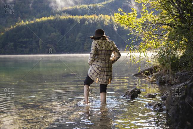 A lady cautiously wading through an alpine lake in Germany