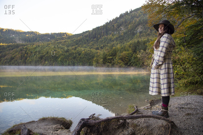 A hipster girl standing by the edge of a lake in Germany