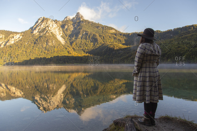 A person standing at the edge of a lake admiring the beautiful view