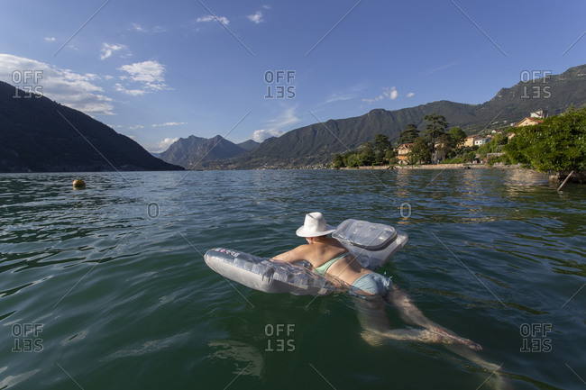 A female sunbather floating on a raft in lake iseo, italy