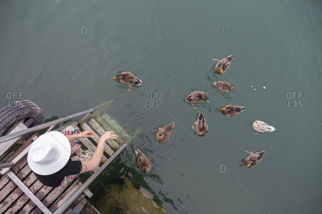 A caucasian woman sitting on a dock feeding ducks on a lake