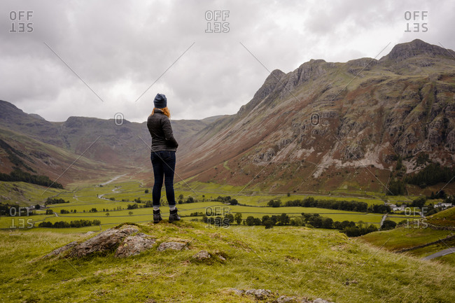 Woman looking out to valley in mountain pass of lake district na