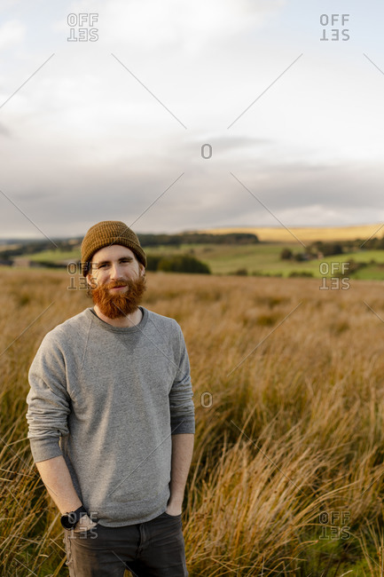 Smiling bearded man in the english countryside at sunset